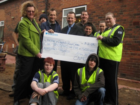 Cotmanhay Neighbourhood Management Group manager Hayley Ash, left, presents the £1,500 donation to Rutland Manor's garden project. Also pictured with the Prince's Trust volunteers and Broomhill College students are, Elaine Mallard, Rutland Manor manager, third right, Ilkeston Round Tables' immediate past chairman Chris Jackson, standing centre, and Mike Baldwin, Broomfield College Horticultural Learning Director, fourth left.